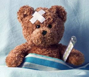 teddy bear in bed with a bandaid and thermometer