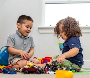 two children playing with toy cars